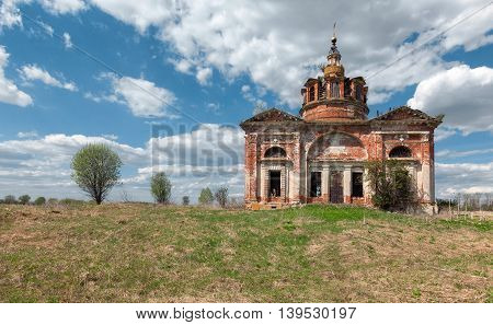Abandoned old brick church in the countryside on the background of blue sky with clouds