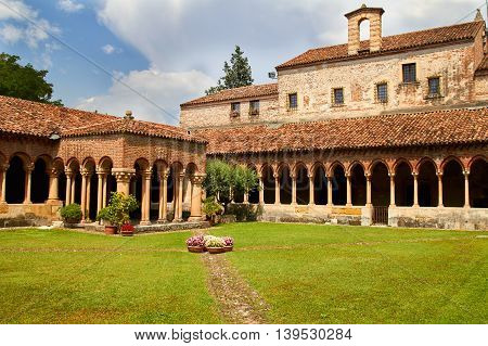 Cloister of San Zeno Cathedral in Verona showing ornate arches and carvings in summer