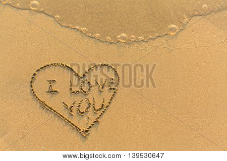 Heart and I Love You - hand-drawn in gentle sea beach sand.