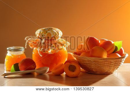 Apricot jam in glass jar arranged with decorations
