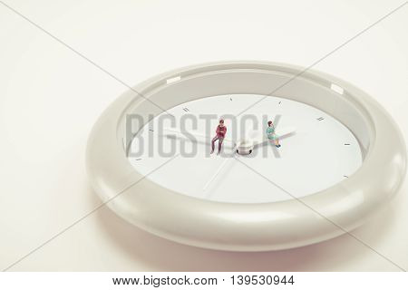 Miniature human doll sitting on the clock