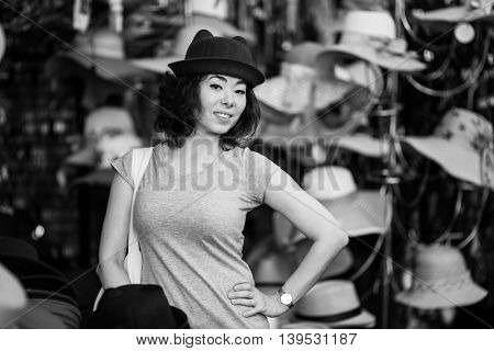 Young asian woman in the store trying on a hat. Black-and-white photo.