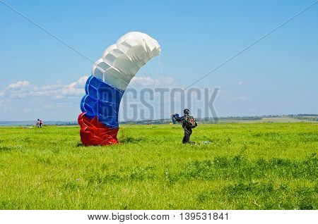 Landing parachutist on the field in summer.