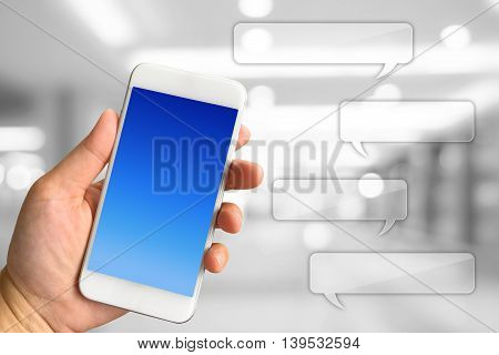 Woman hand holding smartphone against white grey bokeh abstract background Communication concept with speech bubbles