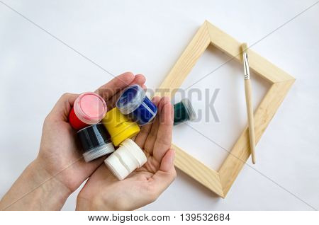 Woman hands holding paints and wood picture frame with paintbrush on the background