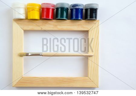 Wood picture frame with paintbrush and six paints. Concept craft