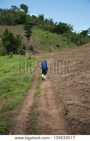 Man Traveler with big backpack mountaineering Travel to the Pre To Lo Su or Pi Tu Kro waterfall heart-shaped waterfall Umphang Tak ,Thailand.