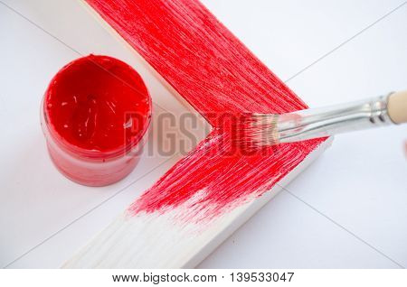 Wood picture frame with paintbrush and red paint. Concept craft
