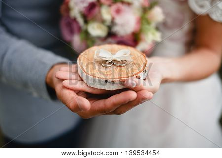 Wedding rings in the hands of the bride and groom