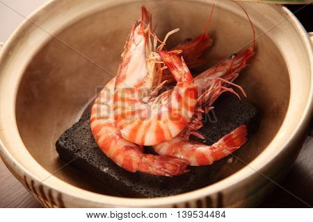 Steamed shrimp by hot rocks in pot in restaurant