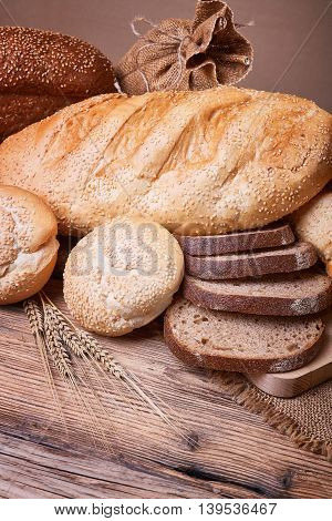 Fresh bread, sweet pastries, baked goods, harvest on the farm, great food, ears of wheat, burlap sack of grain, healthy food, a table of old wood, bread closeup