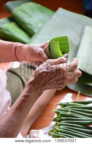Hand of thai old woman posing Fold the banana leaf, artificial