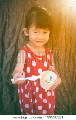 Asian Girl Eating Ice Cream In The Summer Day. Outdoors. Warm Tone.