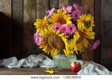 Still life with bouquet of sunflowers in a glass pitcher and Apple.