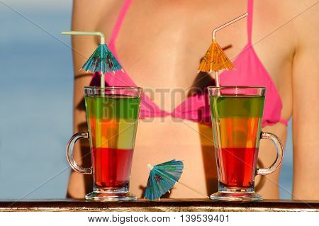 Two colored cocktail and a girl in a swimsuit the sea in the background