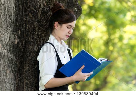 Asian girl student reading book in park at college. High school student.