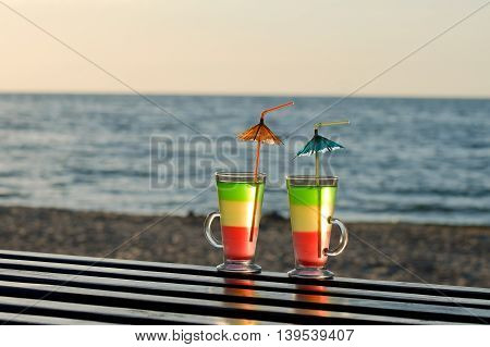 Two cocktails with straws on the beach in the rays of the setting sun against the backdrop of sea shore