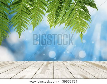 Wood table top on blue blured in background with sunlight. Fern hanging down on Empty table for display.