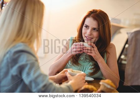 Happy beautyful young woman listening to female friend at coffee shop