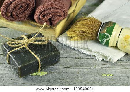 Vintage shaving still life with black soap, shaving brush and towels