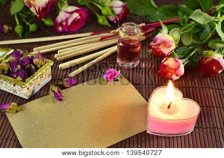 Beautiful spa still life with essential oil, incense sticks, fresh roses and burning candle