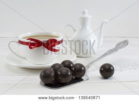Still life with chocolate candies and white decorated tea set