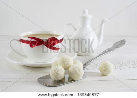 Tea set with white coconut candies and white decorated cup with red bow