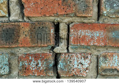 An old wall made of bricks with cracks
