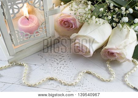 Romantic wedding still life with white roses, pearl necklace and burning candle in lantern