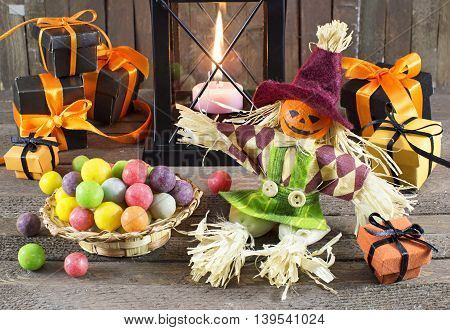 Halloween doll with holiday banner, chocolate candies and burning candle in lantern