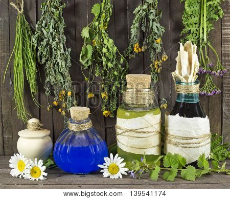 Still life with healing herbs and medical bottles on wooden shelf
