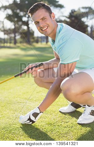 Portrait of confident golfer man placing golf ball on tee while crouching at field