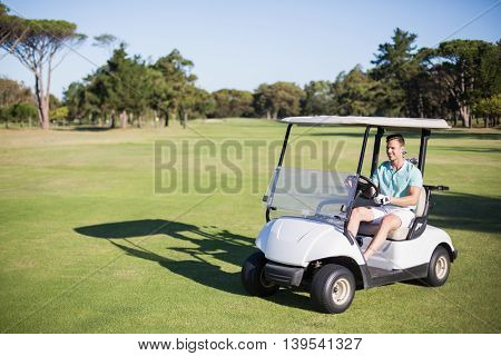 Full length of happy golfer man driving golf buggy on field