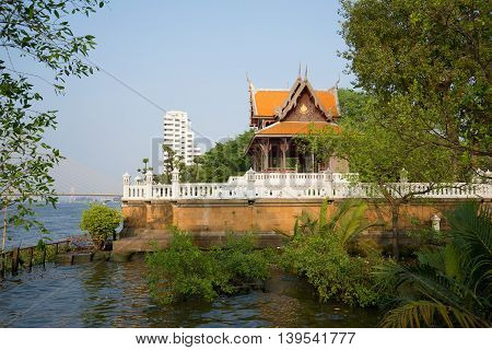 Vintage wooden Buddhist temple on the banks of the Chao Phraya river. Bangkok, Thailand