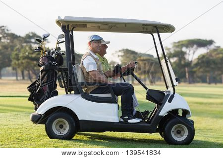 Golfer friends sitting in golf buggy on sunny day