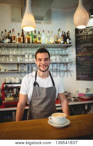 Portrait of confident young male barista with coffee at cafe