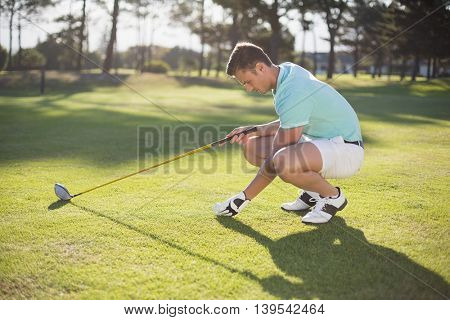 Side view of young man placing golf ball on tee while crouching at field
