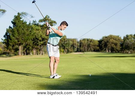 Concentrated golfer man taking shot while standing on field