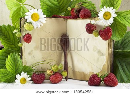 Open cook book with strawberries and flowers