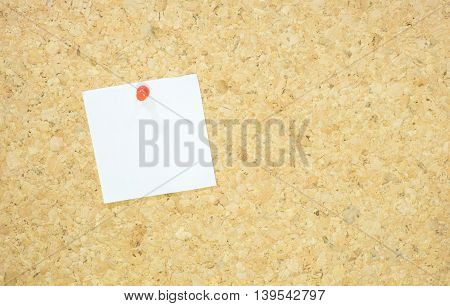 close up notepad with red pushpin on corkboard.