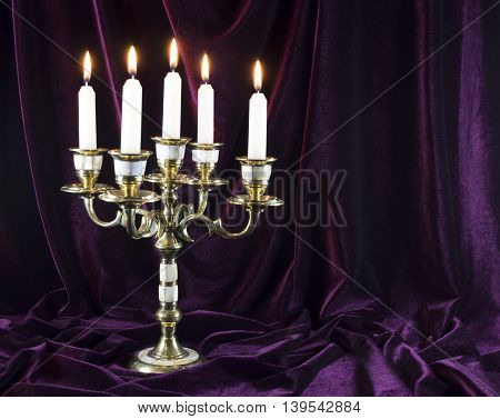 Old candelabrum with burning candles on velvet background