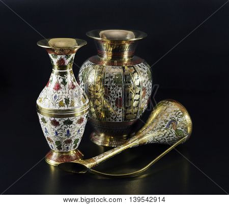 Still life with decorated Indian vases on black