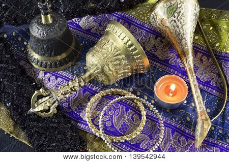 Indian ethnic still life with old ritual bells and candle