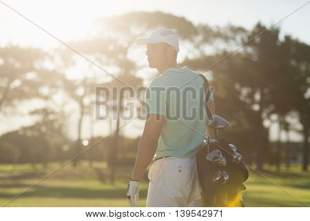 Rear view of golf player carrying bag while standing on field during sunny day