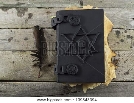 Grimoire magic book with black quill on wooden table