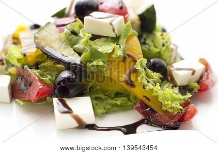 Stack of greek salad on the plate isolated