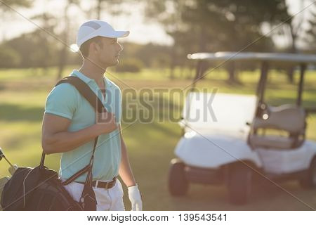 Young golf player carrying bag while standing on field