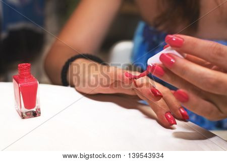 Girl applying nail polish on white table with copy space.