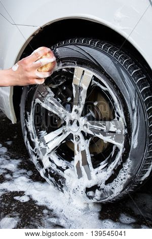 Close Up Of Hand With Sponge Washing Car Wheel