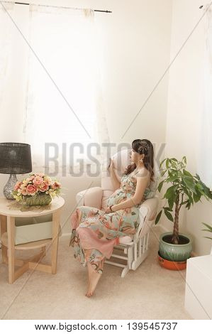 Peaceful pregnant woman with big tummy looking through window at home
